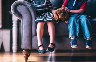 2 kinderen op een bank met een hondje